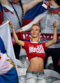 A Russia fan holds Russian flags as she waits for the start of the match before the Euro 2016 group B football match between Russia and Slovakia at the Pierre-Mauroy stadium in Villeneuve-d'Ascq, near Lille on June 15, 2016. / AFP PHOTO / MARTIN BUREAU